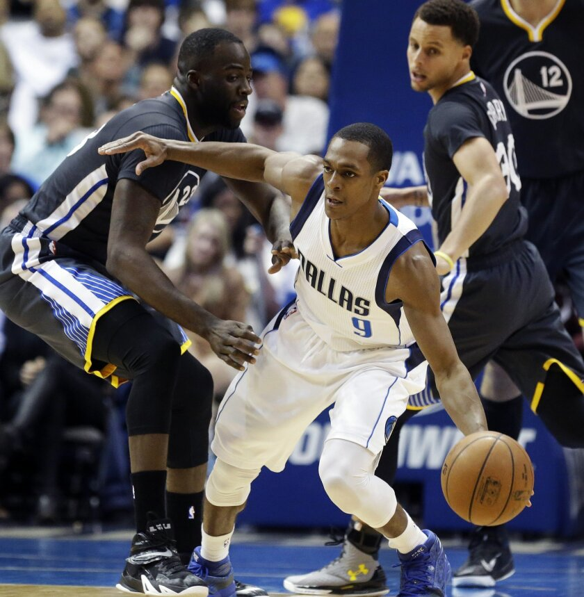 Dallas Mavericks guard Rajon Rondo (9) dribbles against Golden State Warriors Draymond Green (23) as guard Stephen Curry (30) looks on during the first half of an NBA basketball game, Saturday, April 4, 2015, in Dallas. (AP Photo/LM Otero)