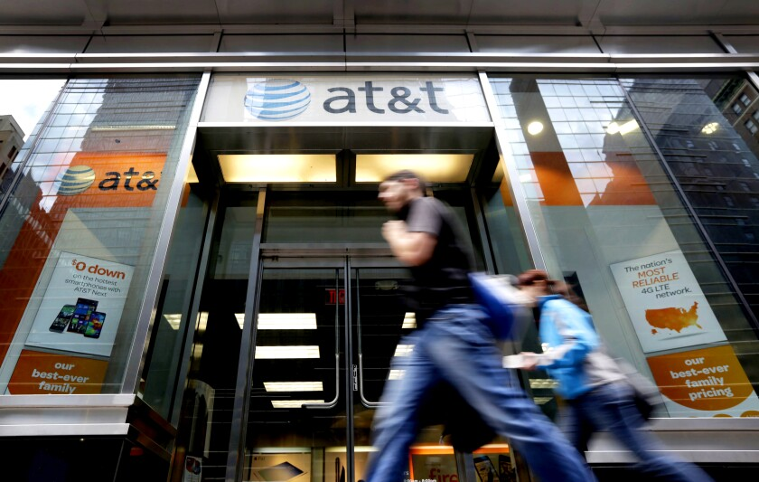 People pass an AT&T store along New York's Madison Avenue.
