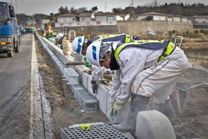 Construction workers did heavy-duty lifting in building a road in Oda. Critics say Japan focused too much money on building roads and infrastructure and not enough on education. (Shiho Fukada / The New York Times)