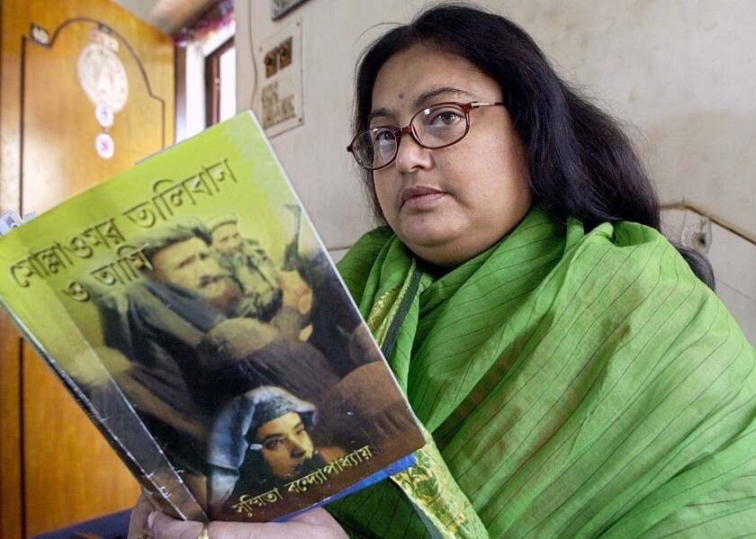 "Indian author Sushmita Banerjee holds one of her Bengali-language novels, ""Mullah Omar, Taliban and Me,"" in Kolkata."