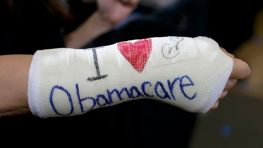 A supporter wears a cast on her broken wrist with 'I (heart) Obamacare' written on it in Boston, Mass. on Oct. 30, 2013.
