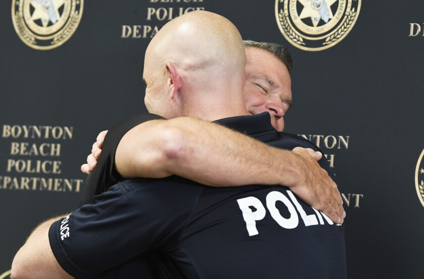 (left) Boynton Beach Police Officer Eric Reynolds and Orange County Sargent David Stull hug after a press conference about finding each other with the help of 23andMe Friday morning in Boynton Beach. Reynolds and Stull are genetic half-brothers, but didn't know it for decades. When both men used 23andMe to find long-lost relatives, they were surprised by the match - and the family resemblance. Add to the surprise, they both are police officers.