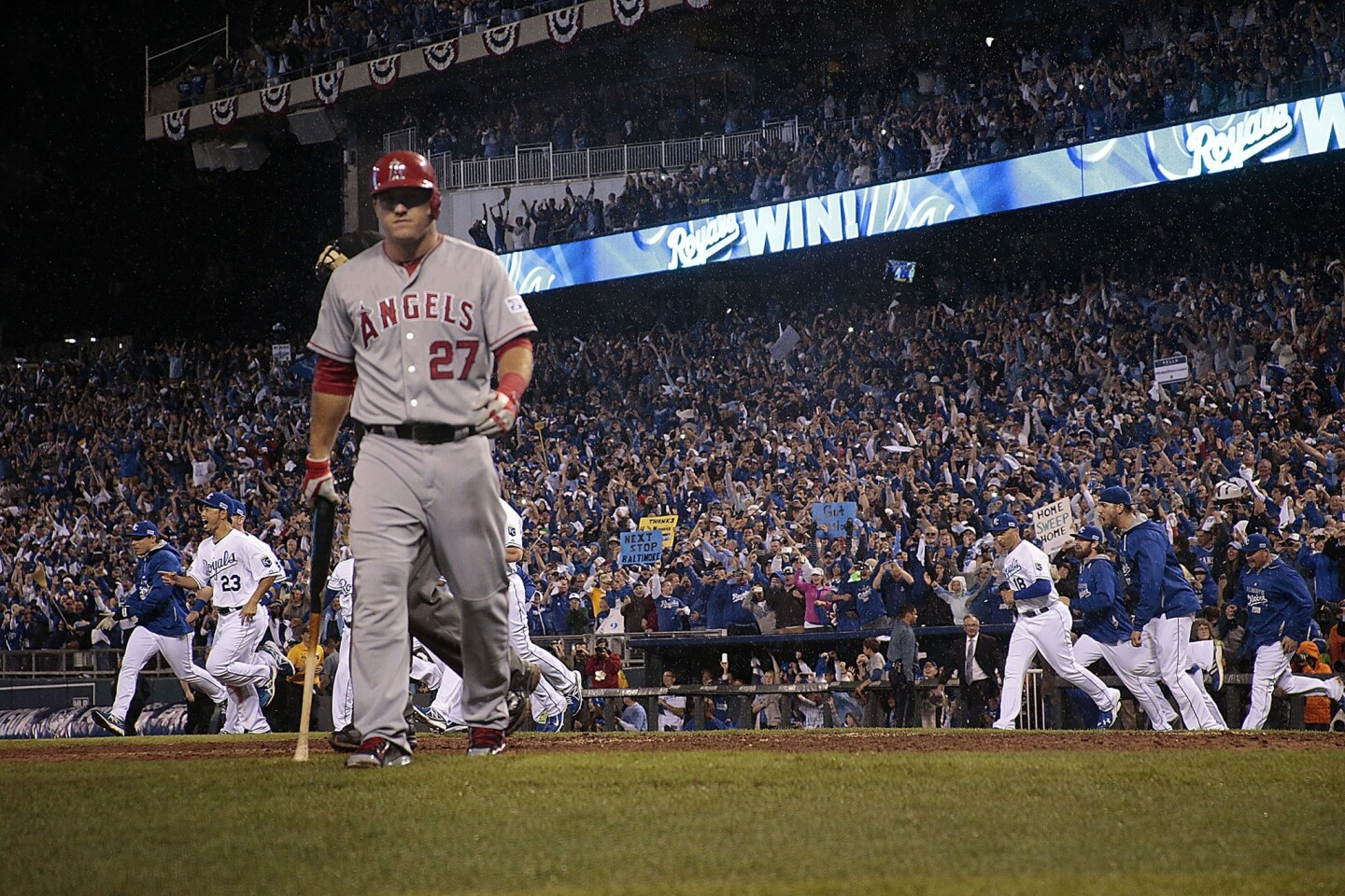 Angels center fielder Mike Trout walks to the dugout as the Kansas City Royals celebrate their series-clinch victory in Game 3 of the ALDS on Sunday.