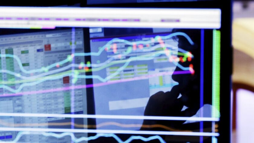 A man is silhouetted on a screen on the floor of the New York Stock Exchange.