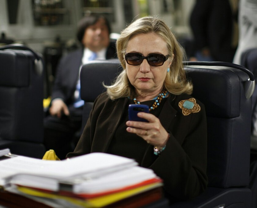 FILE - In this Oct. 18, 2011, file photo, then-Secretary of State Hillary Rodham Clinton checks her Blackberry from a desk inside a C-17 military plane upon her departure from Malta, in the Mediterranean Sea, bound for Tripoli, Libya. Clinton insists that if she pursues the presidency again, it wil