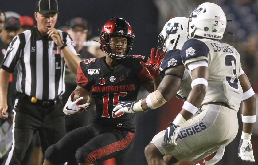 San Diego State's Jordan Byrd fends off the Utah State defenders during last season's game at SDCCU Stadium.