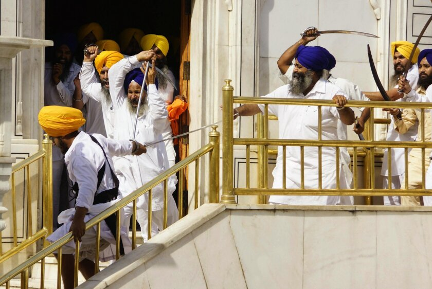 Members of a hardline Sikh group clash with guards of the Sikh's holiest shrine, the Golden Temple, in Amritsar, India, Friday, June 6, 2014. Half a dozen people were wounded Friday as members of a Sikh group brandishing swords and wooden sticks clashed with guards at the shrine in India, an official said. The clash occurred during a ceremony marking the anniversary of the storming of the shrine by the Indian army in June 1984 in the northern city of Amritsar, said Kiran Jyoti Kaur, a Golden Temple management spokeswoman. (AP Photo Prabhjot Gill)