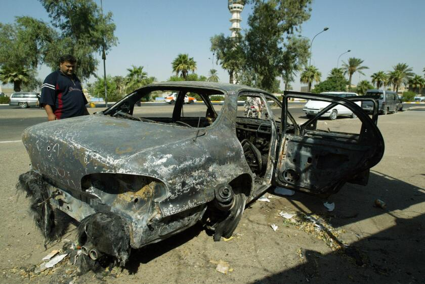 An Iraqi looks at a burned car at the site where Blackwater guards who were escorting U.S. Embassy officials opened fire a week before in Baghdad in 2007.
