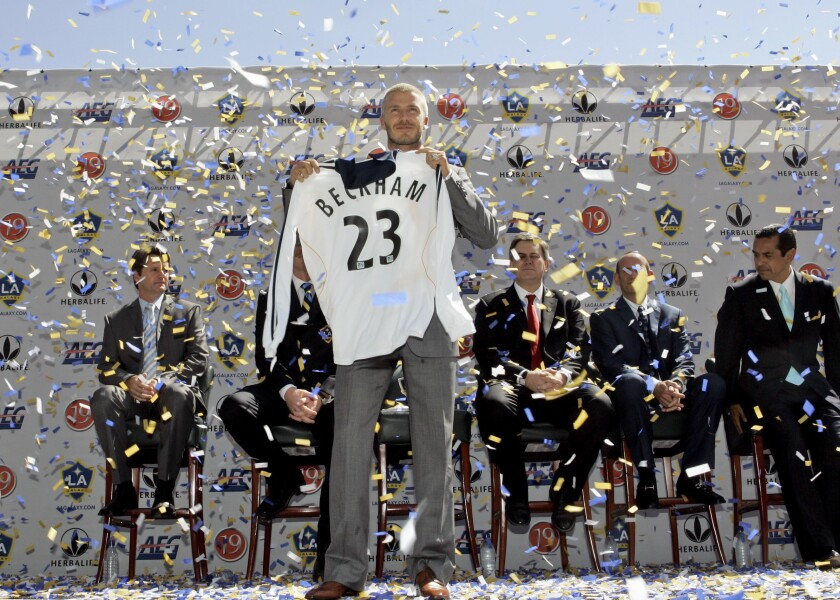 David Beckham holds up his Galaxy jersey during a welcoming ceremony at the Home Depot Center in Carson on July 13, 2007.