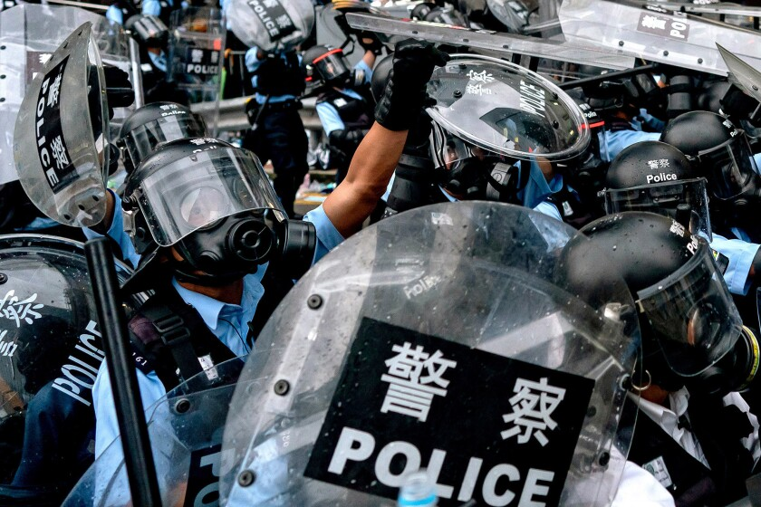 Riot police in Hong Kong surge toward protesters on June 12.