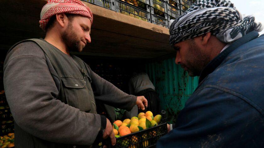 Syrian Kurds load fruit onto a truck headed from Syria's northeastern Kurdish area into Iraq's Kurdistan region.