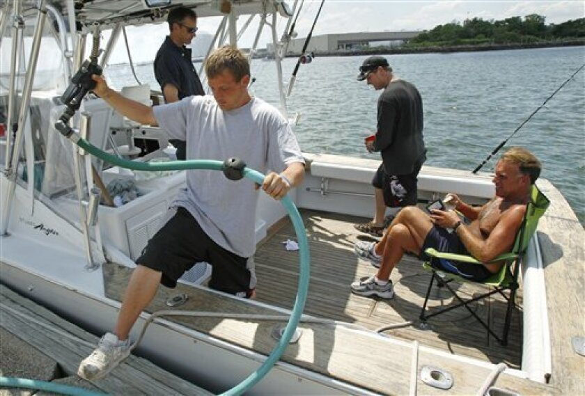 Fuel attendant Derek Locke of Lynn, Mass., steps out of a sports fishing boat after pumping about 150 gallons on board as Ryan Chasse, of Lynn, opens his wallet to pay at the Seaport Landing Marina in Lynn, Mass., Wednesday, June 29, 2011. Retail gasoline prices slipped less than a penny overnight