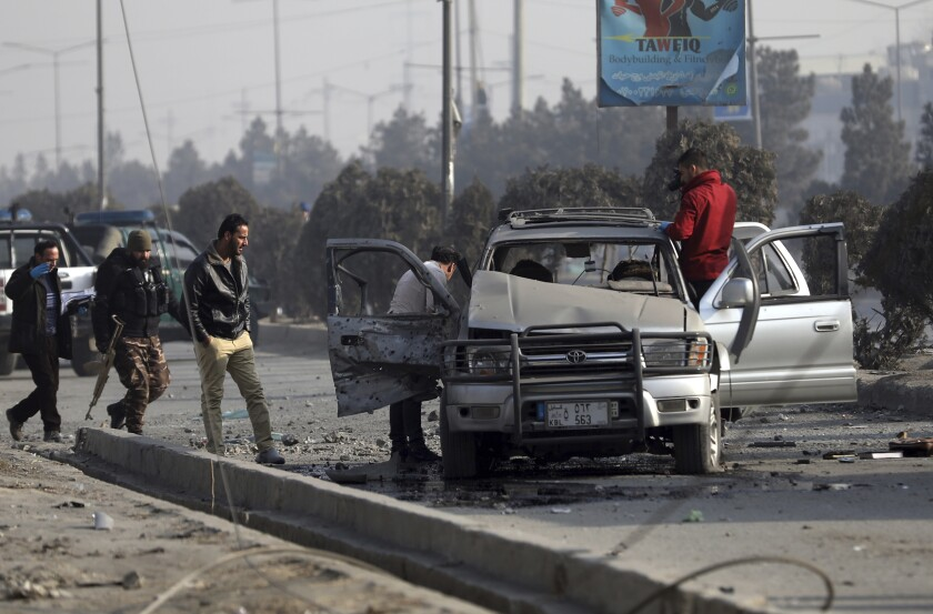 Security personnel inspect the site of a bomb attack in Kabul, Afghanistan, Tuesday, Feb. 2, 2021. A roadside bomb exploded Tuesday in the capital, Kabul, wounding several people. (AP Photo/Rahmat Gul)