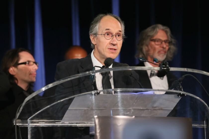 Charlie Hebdo editor-in-chief Gerard Biard accepts PEN/Toni and James C. Goodale Freedom of Expression Courage Award onstage Tuesday night. With him are Charlie Hebdo film critic Jean-Baptiste Thoret, left, and New Yorker cartoon editor Bob Mankoff, right, at the PEN American Center Literary Gala at American Museum of Natural History in New York.