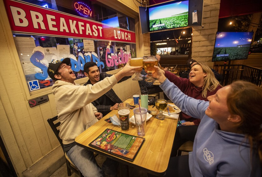Friends toast at Cronies sports bar and grill in Agoura Hills.