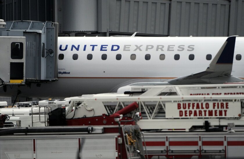 """Emergency vehicles surround a SkyWest Airlines plane, operating as United Express, that made an emergency landing at Buffalo Niagara International Airport, Wednesday, April 22, 2015, in Cheektowaga, N.Y. A SkyWest spokeswoman said one passenger aboard Flight 5622, lost consciousness and the pilots rapidly descended """"out of an abundance of caution."""" (AP Photo/Gary Wiepert)"""