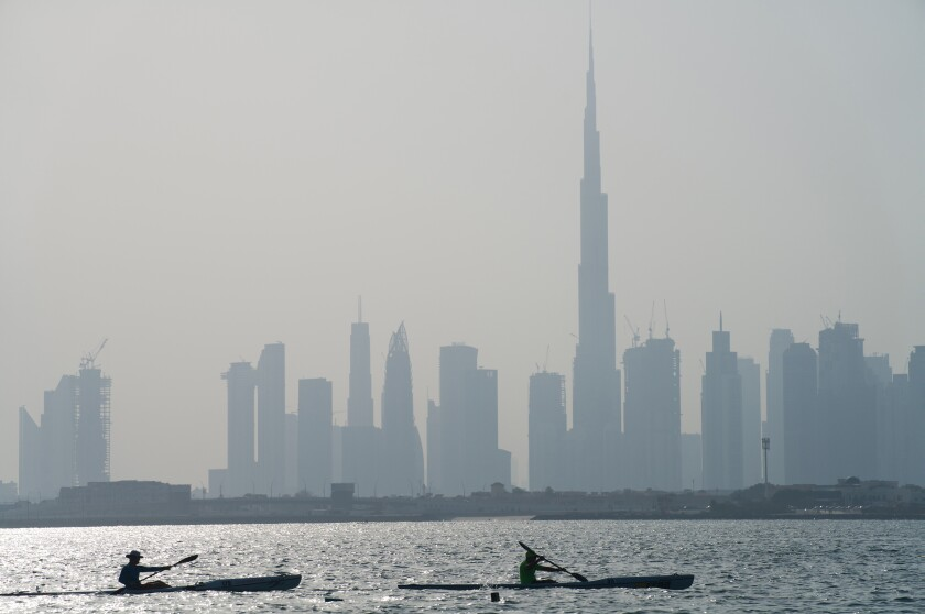 Kayakers race in front of the Burj Khalifa, the world's tallest building, off the coast of Dubai, United Arab Emirates, Friday, June 19, 2020. Dubai has begun allowing organized sports competitions to take place after locking down over the coronavirus pandemic and the COVID-19 illness it causes. Competitions held Friday at the Dubai Offshore Sailing Club were among the first events to be held. (AP Photo/Jon Gambrell)