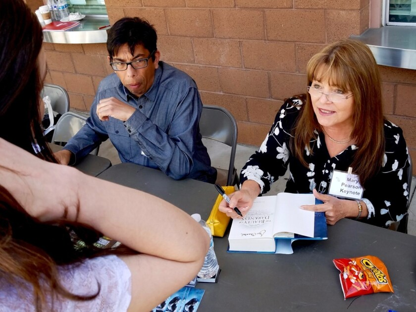 Keynote speaker Mary E. Pearson speaks with a student while signing a copy of one of her books.
