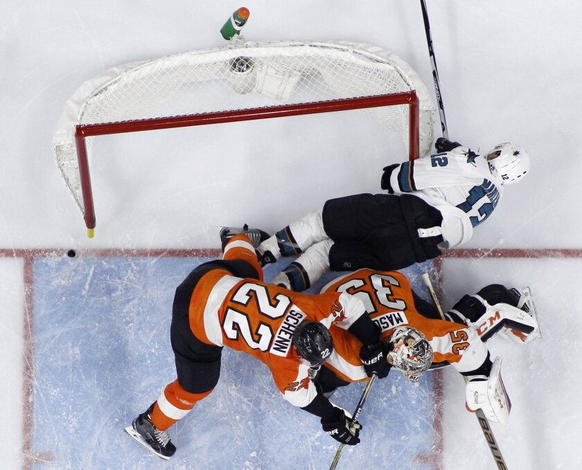 San Jose Sharks' Patrick Marleau (12) collides with Philadelphia Flyers' Steve Mason (35) and Luke Schenn (22) during the third period of an NHL hockey game Thursday, Nov. 19, 2015, in Philadelphia. San Jose won 1-0 in overtime. (AP Photo/Matt Slocum)