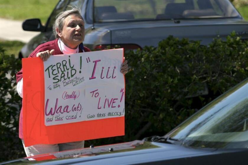 Mary LaFrancis, de Fairfield, Iowa, sostiene una pancarta en protesta por la desconexión de la sonda de alimentación que mantiene viva a Terri Schiavo, una mujer de 41 años que lleva más de la tercera parte de su vida en coma. EFE/Archivo
