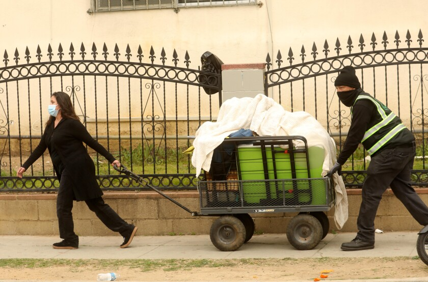 A woman pulls as a man pushes a large wheelbarrow stacked with boxes on a sidewalk.