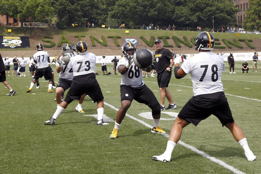 Pittsburgh Steelers tackles Kelvin Beachum (68) and Alejandro Villanueva (78) toss a medicine ball along with the rest of the offensive line during practice at NFL football training camp in Latrobe, Pa. on Sunday, July 26, 2015 . (AP Photo/Keith Srakocic)