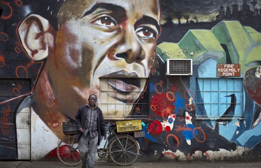 Un hombre posa frente a un mural con la imagen del presidente estadounidense Barack Obama creada por el artista Bankslave en Nairobi, Kenia, el 22 de julio del 2015. Kenia espera la visita oficial del presidente Obama, que visitó Kenia en 2006 cuando era senador. (AP Foto/Ben Curtis)