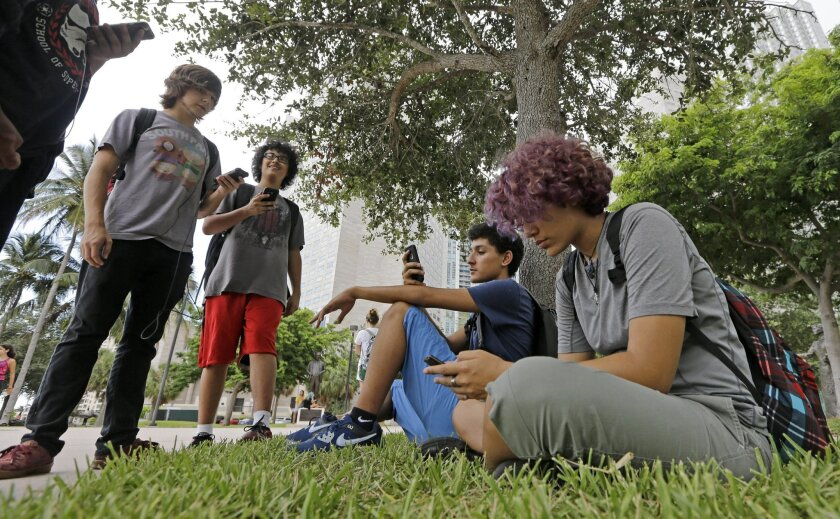 """FILE - In this Tuesday, July 12, 2016 file photo, Pokemon Go players Ana Valentina Ojeda, right, and Jaeden Valdespino, second from right, check their smartphones as they look for Pokemon at Bayfront Park in downtown Miami as the """"Pokemon Go"""" craze has sent legions of players hiking around cities a"""