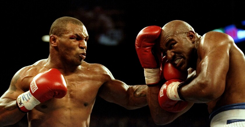 Mike Tyson, left, lands a blow to the chin of Evander Holyfield during their bout June 28, 1997, in Las Vegas.