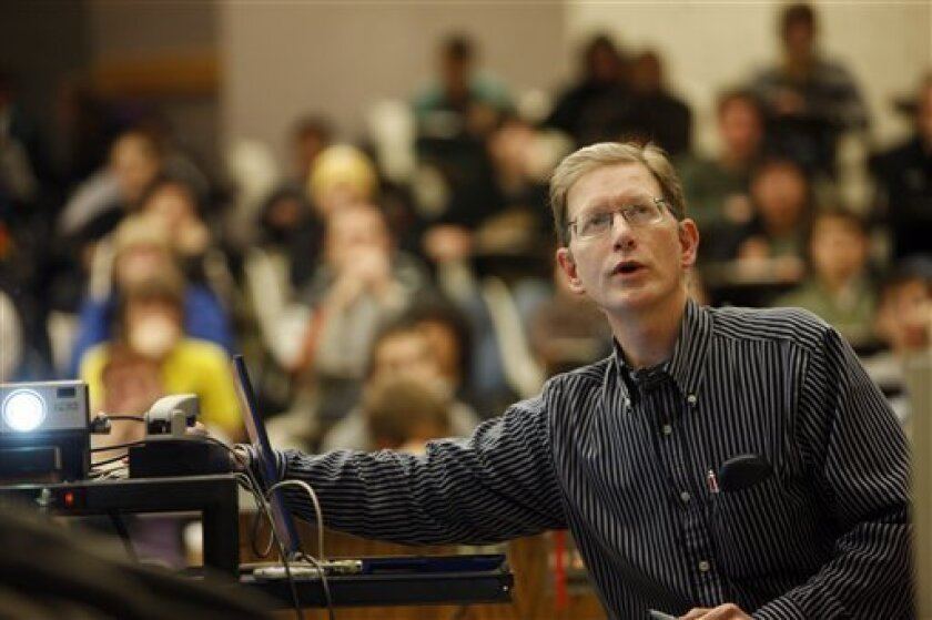 In this photograph taken on Friday, Feb. 26, 2010, Professor Michael Dubson teaches a physics class at the University of Colorado in Boulder, Colo. Some professors like Dubson endorse simple, straightforward devices that stick to multiple choice questions. Others embrace fancier models or newer applications for smart phones and laptops that allow students to query the professor by text or e-mail during the lecture or conduct discussion with classmates _ without the cost of purchasing a clicker. (AP Photo/David Zalubowski)