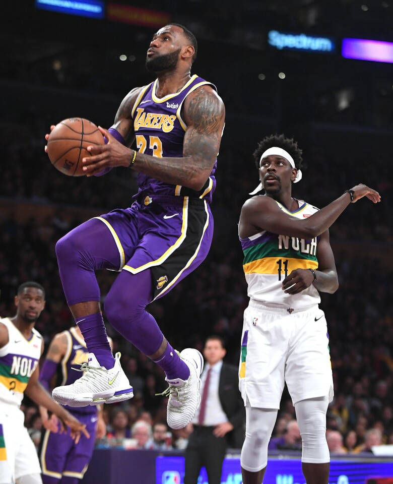 Lakers star LeBron James goes up for a dunk in front of Pelicans guard Jrue Holiday during the second quarter of the Lakers' 125-119 victory at Staples Center on Feb. 27.