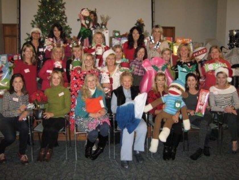 Many caring volunteers of Friends of San Pasqual Academy hosted a wonderful, festive Holiday Party for the foster teens of San Pasqual Academy.  Displaying a few of the donated items that were created or purchased for the foster teens are, seated in front row, Judy Oliphant, Dagmar Helgager, Joyce