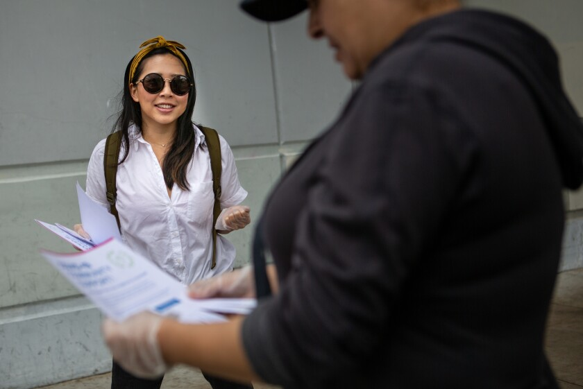 Cristin Lim hands out flyers in Mar Vista offering help to people during the coronavirus pandemic.