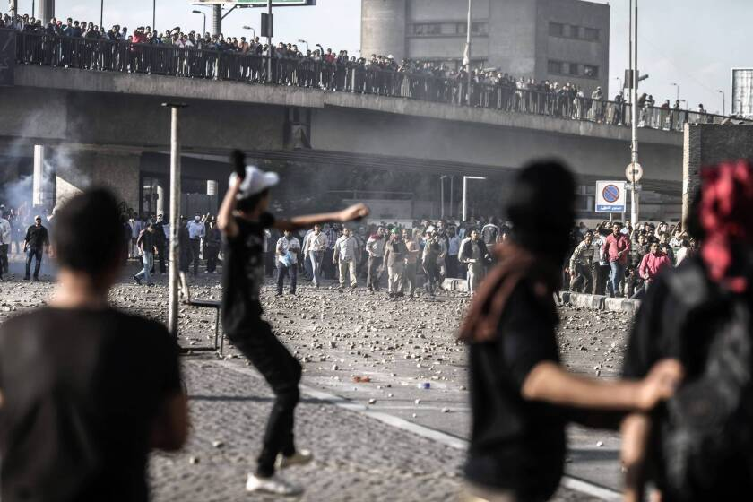 Members of the opposition Black Bloc movement and the Muslim Brotherhood, in the background, throw stones at each other during recent clashes in Cairo. Egyptian President Mohamed Morsi's Islamist backers have called for the courts to be purged of his political enemies.