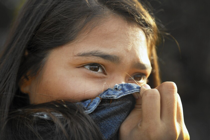 Ashley Hernandez, 23, a youth organizer with Communities for a Better Environment, holds her jacket over her nose as fumes emanate from a residential oil drilling operation in her Wilmington neighborhhod.