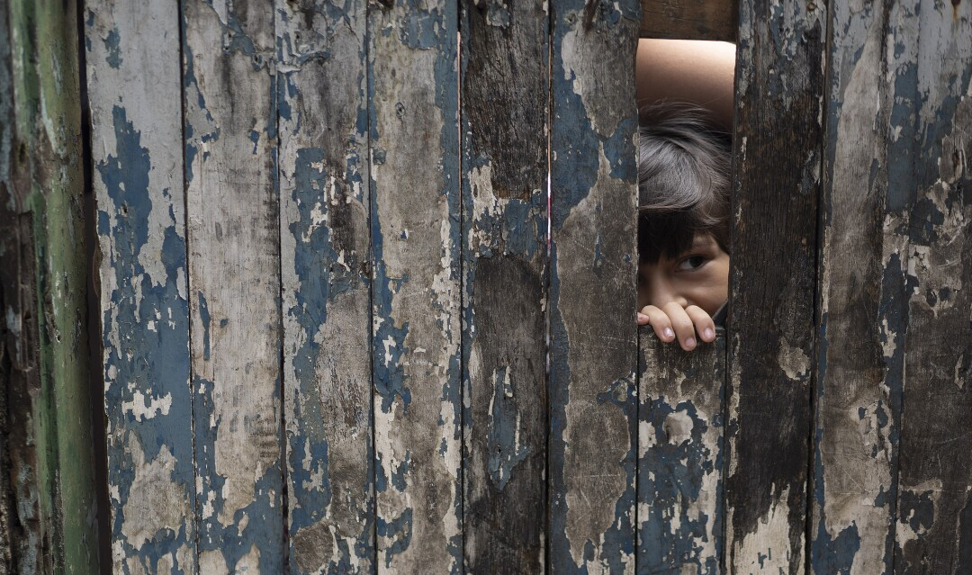 A boy peeks from the doorway of his home in the Rocinha slum of Rio de Janeiro.