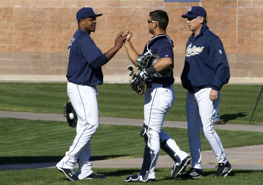 Pitcher Edinson Volquez greets catcher Eddy Rodriguez with Manager Bud Black during the first workout day of Padres spring training Wednesday in Peoria, Arizona.