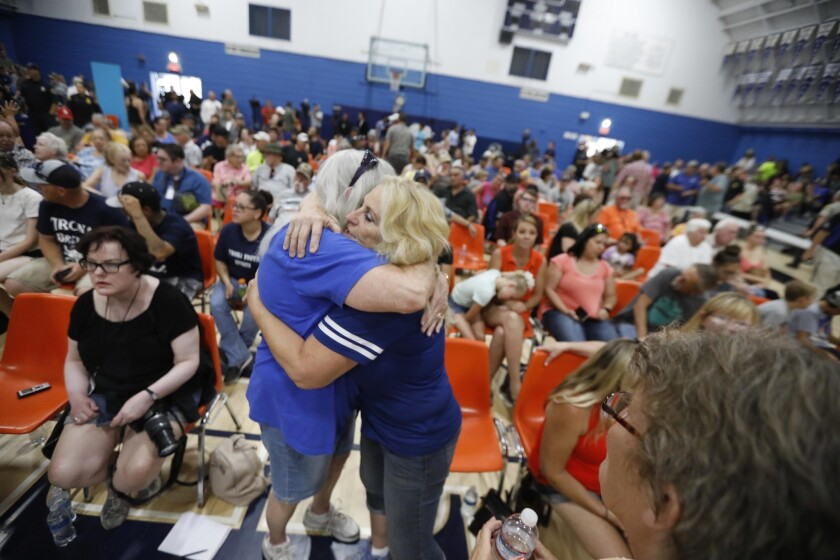 At Trona High School, Lauretta Eldridge, right, hugs Joyce Surles of Trona. Residents gathered to hear updates and voice their concerns at a town hall meeting. Eldridge, who grew up in the town, came in from Bakersfield to look after her parents.