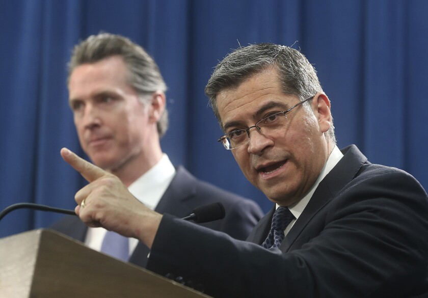California Attorney General Xavier Becerra, right, accompanied by Gov. Gavin Newsom