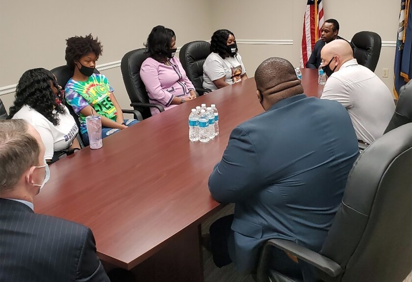 Tamika Palmer, far left, the mother of Breonna Taylor, and other family members meet with Kentucky Attorney General Daniel Cameron on Wednesday, Aug. 12, 2020, in Louisville, Ky. Taylor was fatally shot by Louisville police on March 13, and protesters have called for Cameron to charge the officers involved. Cameron has called for patience while the investigation is ongoing. (Christopher 2X via AP)