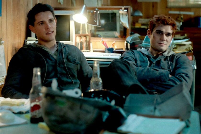 Two young men sit in chairs next to each other in front of a desk in a cluttered office.