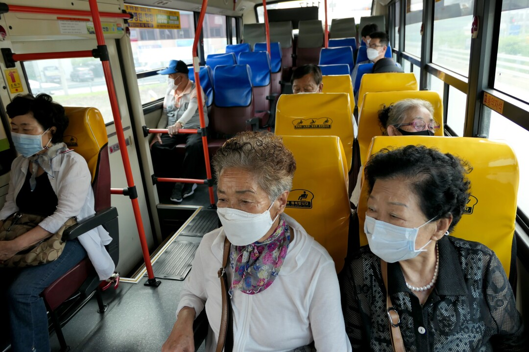 Older people ride a bus with some empty seats
