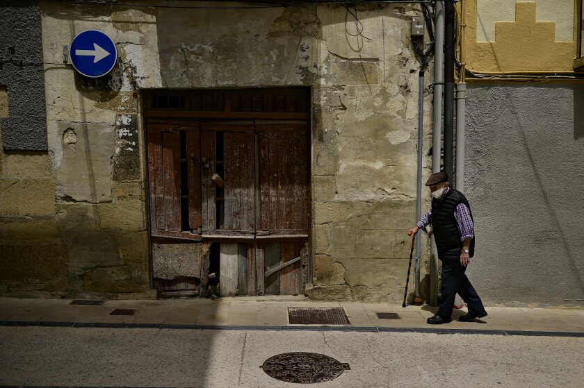An elderly man go for a walks while wearing a face mask to protect against coronavirus, in Lumbier, northern Spain, Sunday, June 7, 2020. (AP Photo/Alvaro Barrientos)