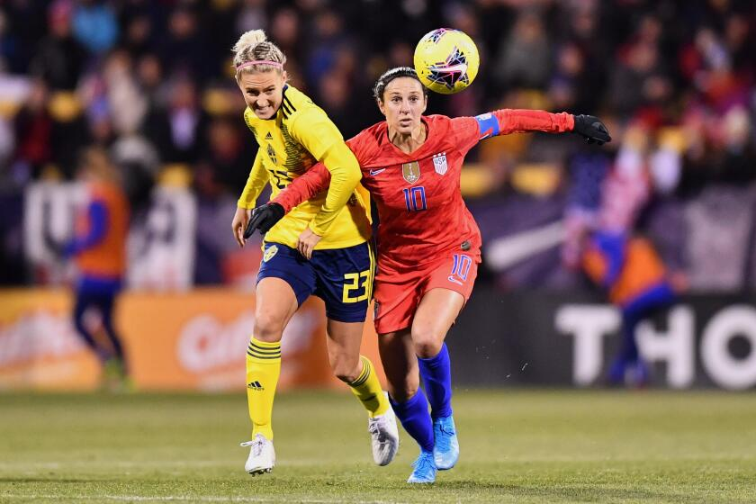Carli Lloyd, right, battles Sweden's Emma Kulberg during a match in November.