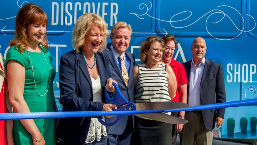 Costa Mesa Mayor Katrina Foley uses giant scissors to cut the dedication ribbon during a ceremony Friday to celebrate the recent launch of the Costa Mesa Line. The free shuttle transports passengers in and around the South Coast Metro area.
