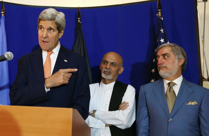 """FILE - In this Friday, Aug. 8, 2014 file photo, U.S. Secretary of State John Kerry, left, speaks as Afghan presidential candidates Ashraf Ghani Ahmadzai, center, and Abdullah Abdullah listen during a joint press conference in Kabul, Afghanistan. """"Radicals"""" backing Abdullah could foment postelection violence if he isn't given an equitable share of power, his spokesman warned Saturday, Sept. 6, 2014 ahead of a meeting with his rival aimed at resolving a monthslong election dispute. U.S. Secretary of State John Kerry helped broker an agreement this summer under which all 8 million ballots would be recounted, a process which was concluded Friday. (AP Photo/Rahmat Gul, File)"""