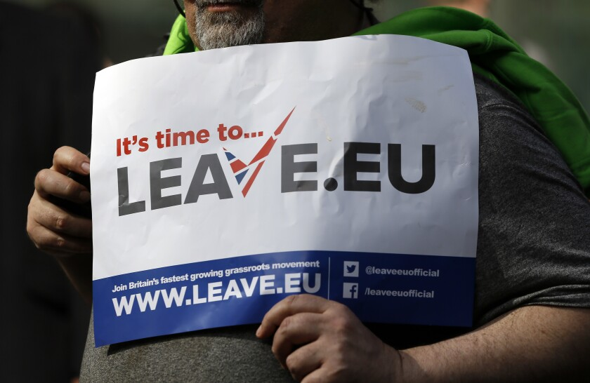 FILE - In this Thursday, March 31, 2016 file photo, a 'Leave' supporter holds a banner near the Electoral Commission, in London. Five years ago, Britons voted in a referendum that was meant to bring certainty to the U.K.'s fraught relationship with its European neigbors. Voters' decision on June 23, 2016 was narrow but clear: By 52 percent to 48 percent, they chose to leave the European Union. It took over four years to actually make the break. The former partners are still bickering, like many divorced couples, over money and trust. (AP Photo/Kirsty Wigglesworth, File)
