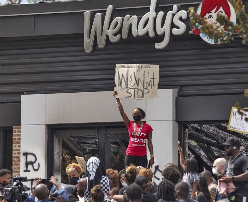 People hold a rally at Wendy's on University Avenue in Atlanta on Sunday, June 14, 2020. Rayshard Brooks died after a confrontation with police officers at the fast food restaurant in Atlanta on Friday, June 12. (Steve Schaefer/Atlanta Journal-Constitution via AP)