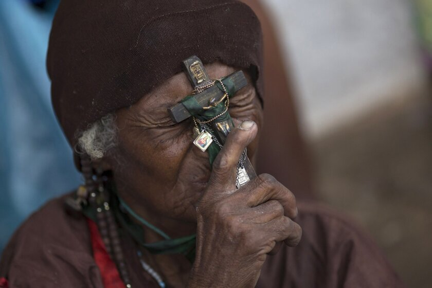 In this Oct. 31, 2015 photo, a beggar presses a crucifix to her forehead as she stands before a statue of Padre Cicero in Juazeiro do Norte, Brazil, during a pilgrimage in honor of the late Brazilian priest.  Rev. Cicero Romao Batista became renowned for helping the poor and improving the lives of