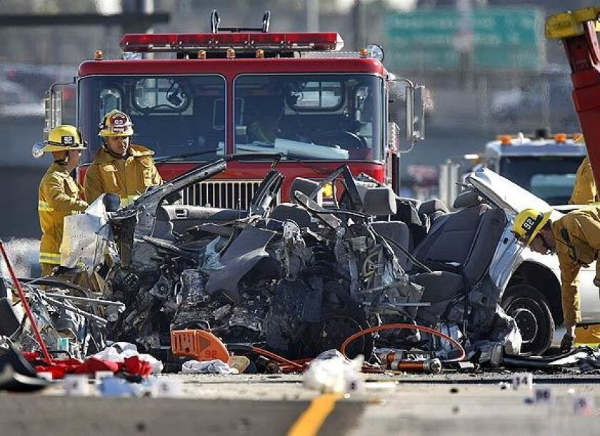 Los Angeles Fire Dept. firefighters view the wreckage of a Toyota Camry involved in a double-fatality accident on the eastbound side of 10 Freeway early Wednesday morning.